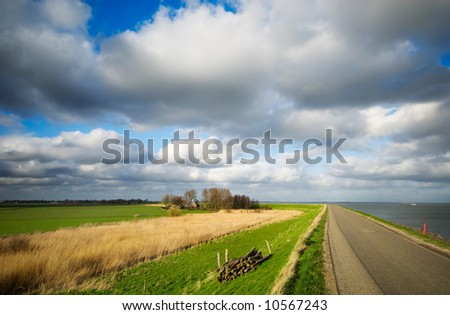 """beautiful sky on a country road in the netherlands with a lake called the """"ijsselmeer"""" to the right - stock photo"""