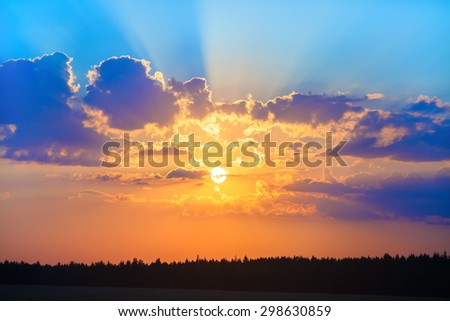 Beautiful sky with bright sun and beautiful cumulus clouds. Sunset over the forest. - stock photo
