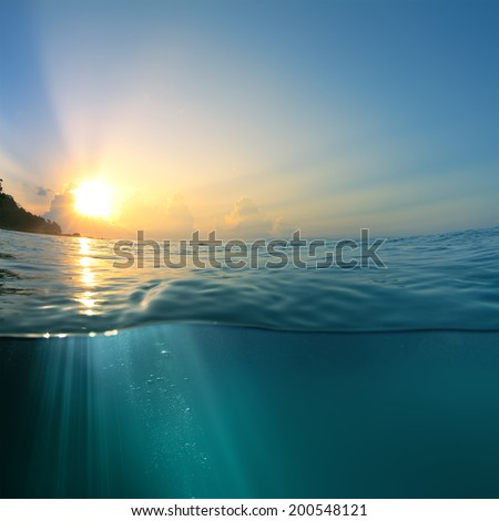 Beautiful sky with the sun image splitted by waterline. Air bubbles and sunrays underwater - stock photo