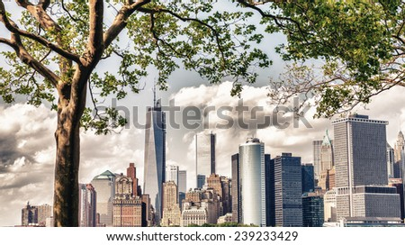 Beautiful skyline of Lower Manhattan framed by Governors Island trees in summer - New York City. - stock photo