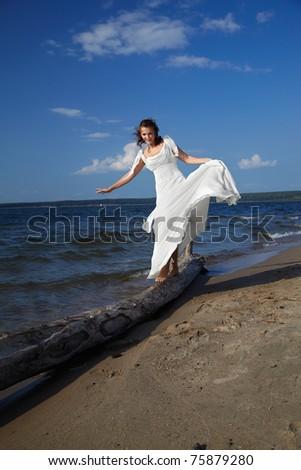 beautiful slavonic bride on sea shore balancing on trunk - stock photo