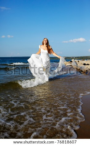 beautiful slavonic bride running in sea waves with bridal in her hands