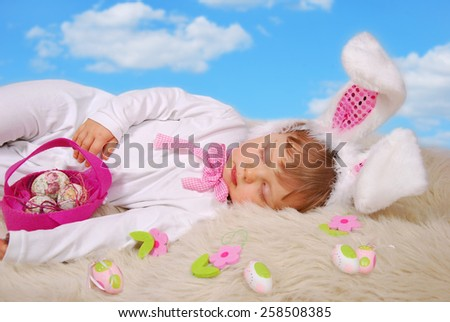 beautiful sleeping baby girl in easter bunny costume with eggs in pink felt basket  - stock photo