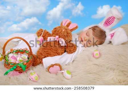 beautiful sleeping baby girl in easter bunny costume with eggs in wicker basket - stock photo