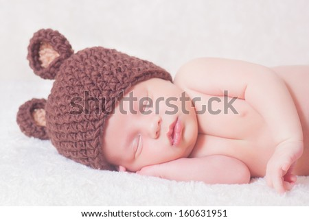 beautiful sleeping newborn baby wearing a striped hat - stock photo