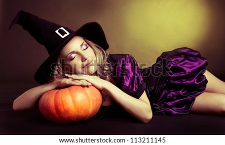 beautiful sleeping witch with a pumpkin, against yellow studio background - stock photo