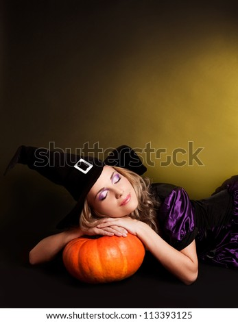 beautiful sleeping witch with a pumpkin, against yellow studio background, copy-space for your text on the top - stock photo