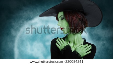 Beautiful sleeping witch with green skin on full moon background. Halloween, horror theme - stock photo
