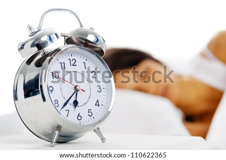 Beautiful sleeping woman resting in bed with alarm clock ready to wake her in the morning. - stock photo