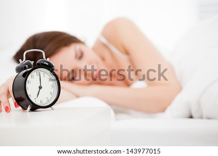 Beautiful sleeping woman resting in bed with alarm clock ready to wake her in the morning