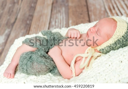 beautiful sleepy swaddled newborn baby in knitted hat  - stock photo