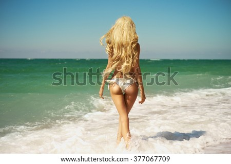 Beautiful slender blonde at the sea. Summer travel photos