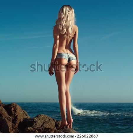 Beautiful slender blonde on sea. Summer travel photos - stock photo