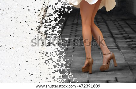 Beautiful slender female legs in a dark alley on the background of the spots with black paint (double exposure)