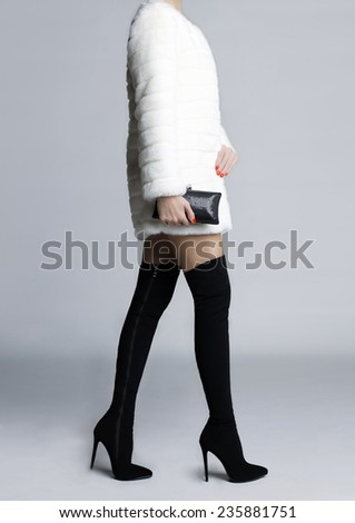 Beautiful slender female legs in elegant boots stockings - stock photo