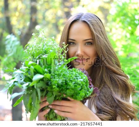 Beautiful slender girl holding healthy fresh greens.  - stock photo