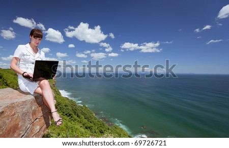 beautiful slender girl with a laptop on the nature - stock photo
