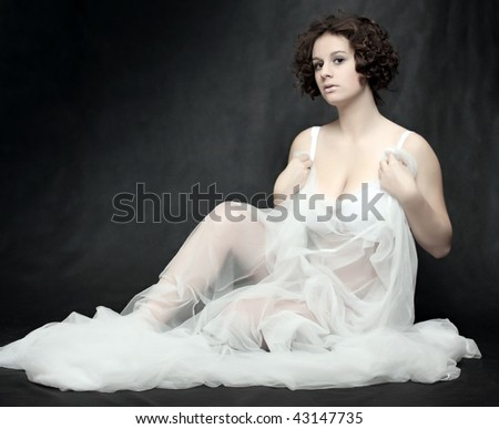 Beautiful slenderness young woman in bridal veil on black background. Low key studio shot. Great for calendar. - stock photo