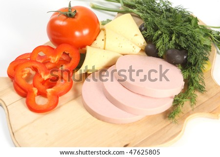 Beautiful sliced food arrangement with sausage, cheese, olives and greenery