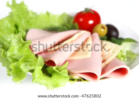 Beautiful sliced food arrangement with sausage, ripe cherry tomatoes, cheese and greenery - stock photo