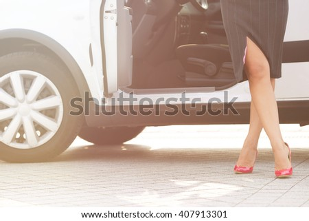 Beautiful slim and slender crossed woman's legs near car. Pretty lady in grey skirt posing on pink high heels in the city. Toned image. - stock photo