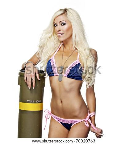 Beautiful slim blond woman posing beside bomb. - stock photo