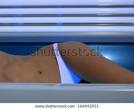 Beautiful slim blonde girl tans in the solarium - stock photo
