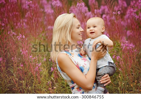 Beautiful slim blonde mom hugs adorable smiling baby boy on the background of grass fireweed in the summer - stock photo