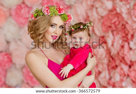 Beautiful slim blonde mom in red dress and a wreath of flowers is holding his young daughter on a background of pink flowers