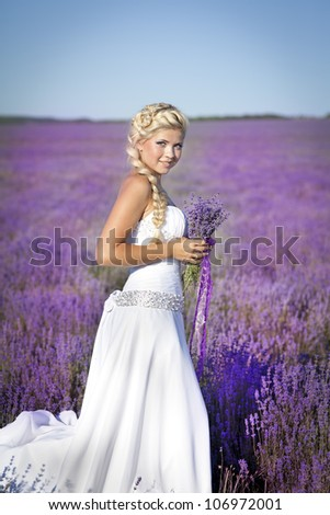 beautiful slim bride in luxurious wedding dress in purple lavender flowers. Fashion romantic happy woman with blond hair. Smiling girl in sunset over summer lavenda field waiting for groom -Provence
