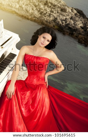 beautiful slim bride in red wedding dress playing grand piano on sunset beach. Fashion romantic stylish arabian young girl musician with long glossy healthy hair. Spring - summer - stock photo
