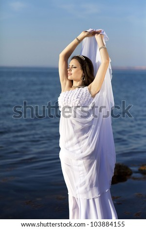 beautiful slim bride in wedding dress on sunset beach near sea. young woman in Greek  goddess style with diamond tiara and jewelery. Fashion stylish romantic girl with glossy hair. Spring - summer - stock photo