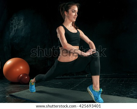 Beautiful slim brunette doing some stretching exercises in a gym - stock photo