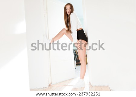Beautiful slim fashionable brunette posing at home against the sun - stock photo
