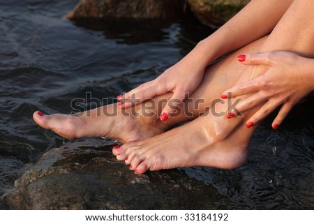 Beautiful slim feet and hands of the young girl on seacoast, close up