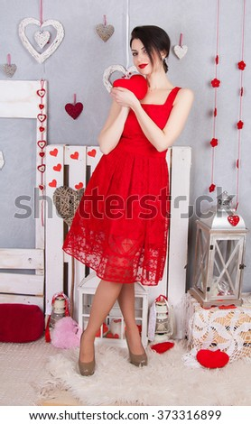 Beautiful slim girl in the red dress openwork. Young sexy model in a red dress with slim long legs standing on a bright background of hearts. A girl holding a red heart - stock photo