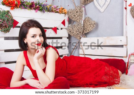 Beautiful slim girl in the red dress openwork. Young sexy model with red lips and red dress lying on the pale. - stock photo