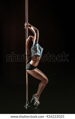 Beautiful slim girl with pylon. Female pole dancer woman dancing on a pole on a black background.