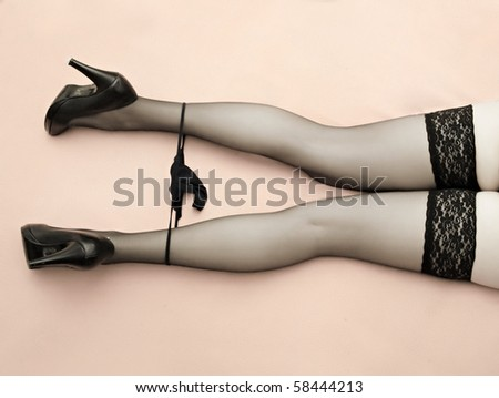 Beautiful slim legs in black nylons on a pink background. Great image for calendar. - stock photo