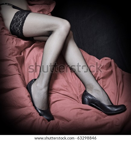 Beautiful slim legs in black nylons on a pink background. Vintage style photography - great for calendar. - stock photo