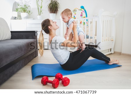 Beautiful slim mother playing with her baby on fitness mat at home