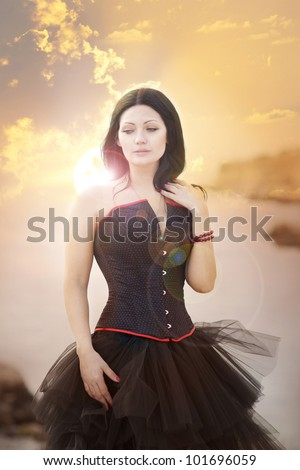 beautiful slim rich woman in luxurious dress on sunset beach. Fashion romantic stylish arabian young girl with long glossy healthy hair. Gothic bride Spring - summer - stock photo