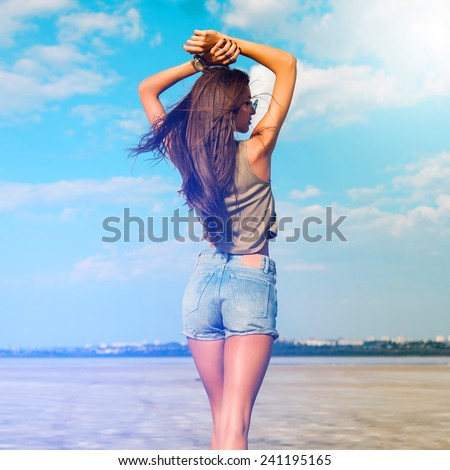 Beautiful slim tanned fitness   girl 's back  with  hands on top. Posing outdoor in stylish jeans shorts. Soft light.  - stock photo
