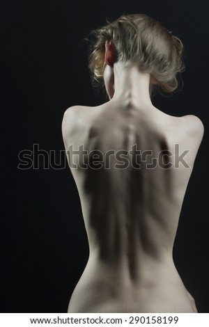 Beautiful slim undressed female body perfect shape sitting with back view on black background, vertical picture - stock photo