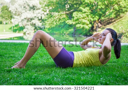 beautiful slim woman doing exercises for abdominal muscles in park - stock photo