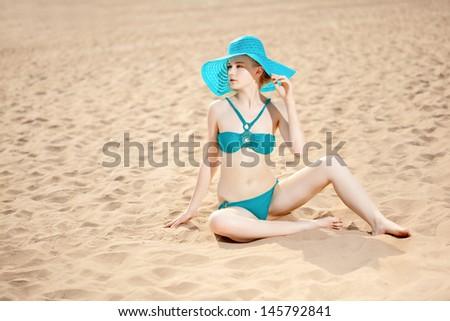Beautiful slim woman on the beach by the sea  - stock photo