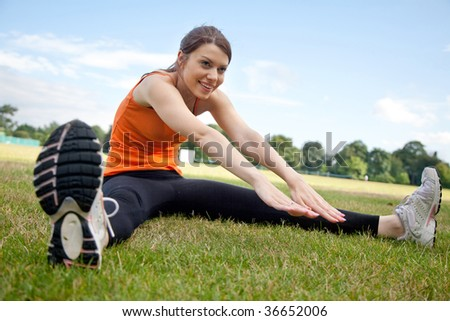 Beautiful slim woman stretching at the park - stock photo