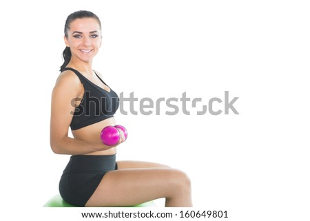 Beautiful slim woman using pink dumbbells sitting on an exercise ball smiling at camera