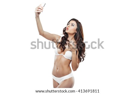Beautiful slim woman wearing white lingerie. Studio shot of young seductive woman isolated on white background. Woman making selfie with mobile phone - stock photo