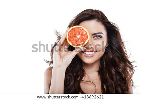 Beautiful slim woman wearing white lingerie. Studio shot of young seductive woman isolated on white background. Woman smiling and holding grapefruit - stock photo